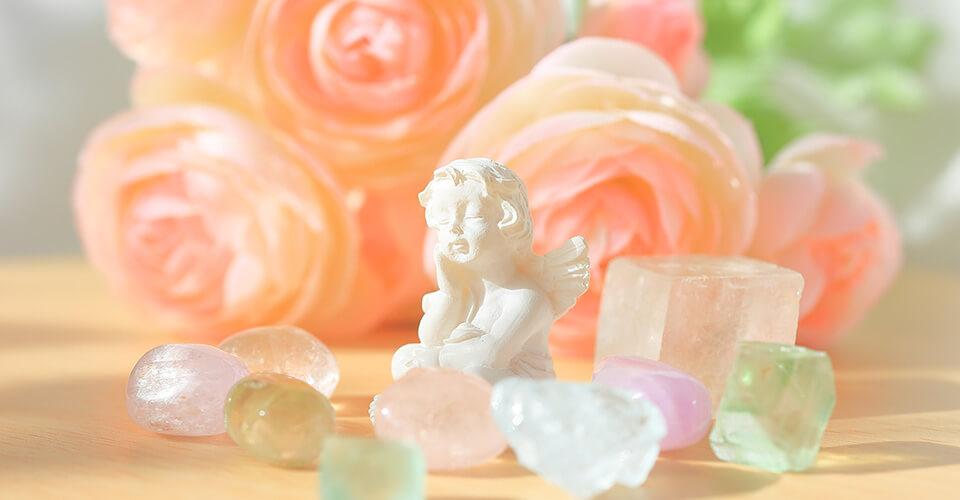 バラの花とパワーストーンに囲まれた天使の像